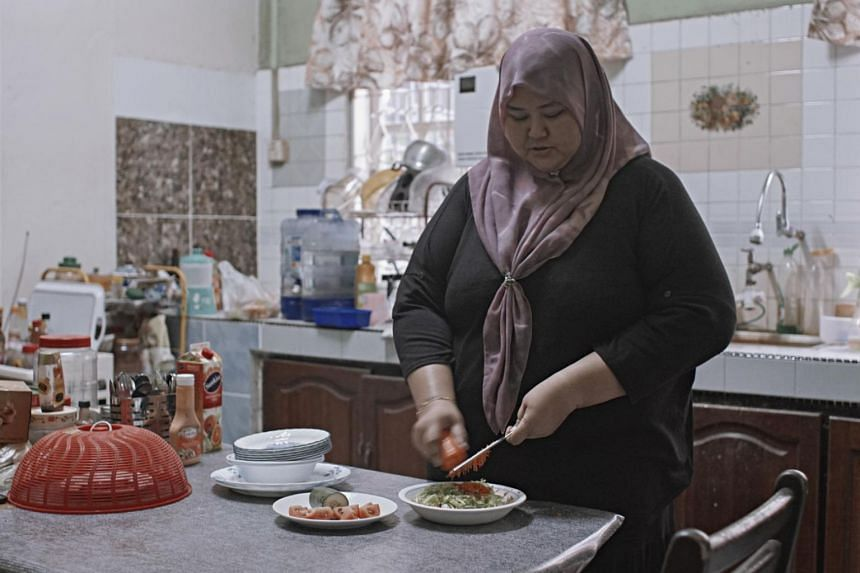 A woman taking part in a nutrition programme prepares a salad for lunch at home in Kota Baru, Malaysia.