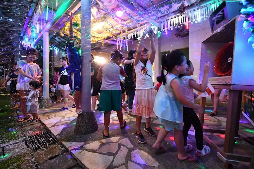 Residents having fun at the snow party with the Christmas decorations put up by Mr Tan Koon Tat, at Woodlands Street 13.