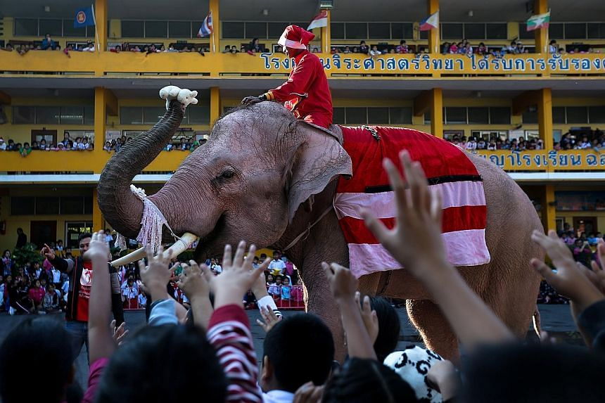 """Four elephants and their mahouts dressed in Santa Claus suits handed out toys, balloons and snacks to delighted children of a school in Thailand's old capital of Ayutthaya yesterday. """"I'm so glad because elephants are coming. And they are giving pres"""