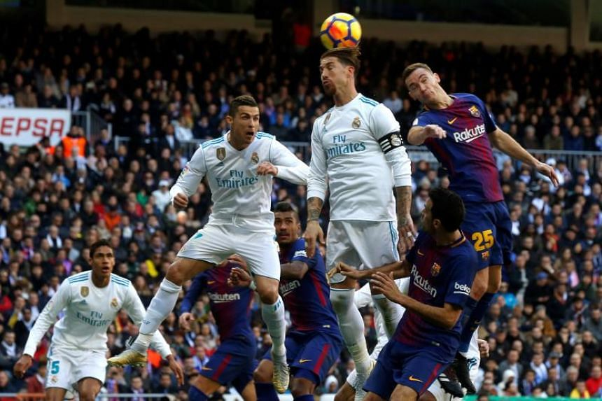 Real Madrid's players Cristiano Ronaldo (second from left) and Sergio Ramos (third from left) in action against FC Barcelona's Thomas Vermaelen (second from right) and Sergio Busquets (right) during the match at the Santiago Bernabeu stadium in Madri