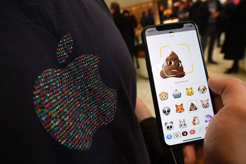 An Apple staff member poses with a new iPhone X showing emoji features in Apple's Regent Street store in London.