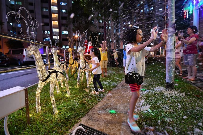 Residents having fun at the snow party with the Christmas decorations put up by Mr Tan Koon Tat at Woodlands Street 13.