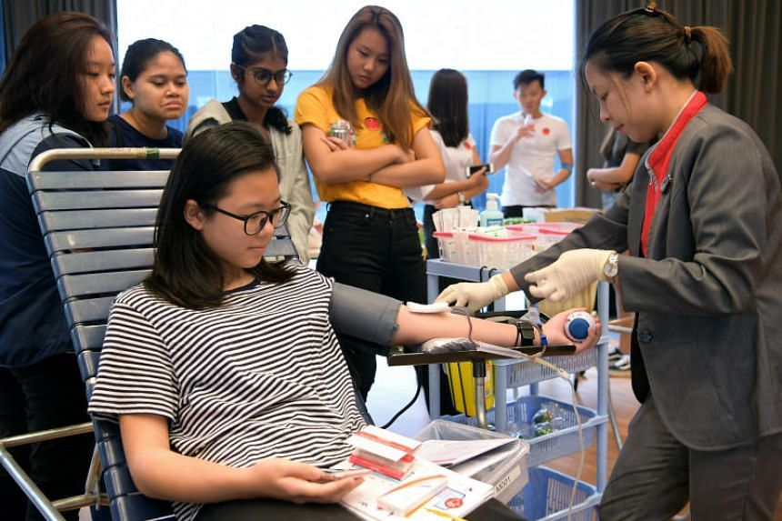 HSA blood professional assistant Marienelle Padre helps CHIJ student Hilda Lam with her first blood donation at *Scape, on Dec 23, 2017.