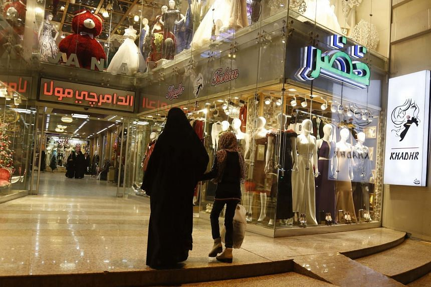 An Iraqi woman and a child walk past the window display of a shop selling women's clothes in Karbala.