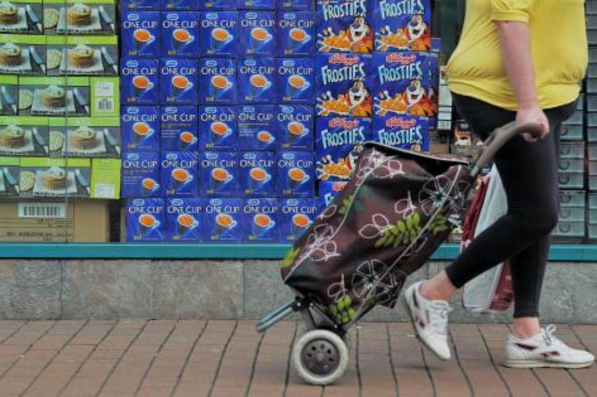 A woman pulls her shopping basket as she walks past a store displaying food and drinks goods in it's window, in Hounslow, west London on May 18, 2010.
