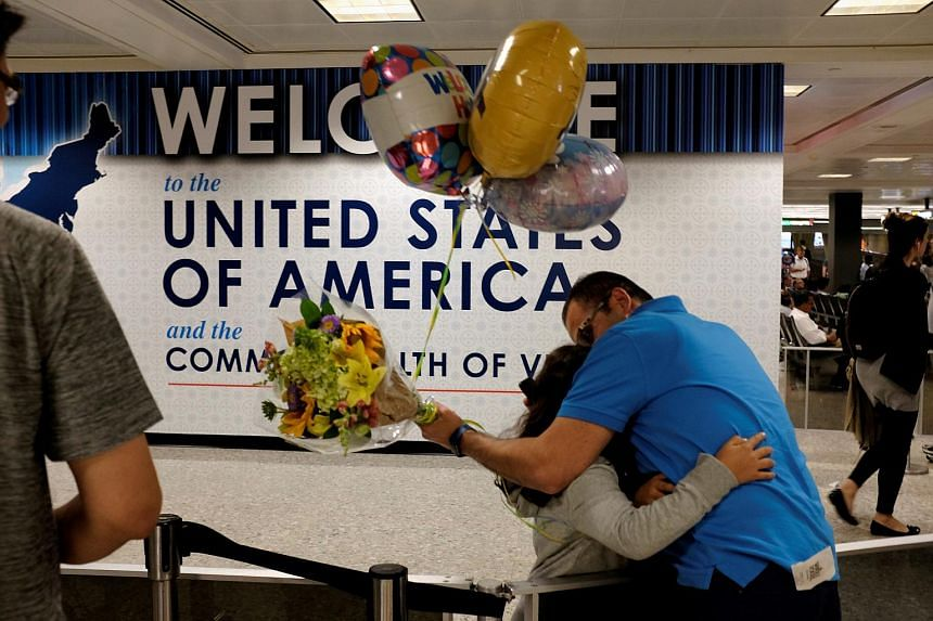 Ahmed Khalil, an Egyptian national residing in the US, hugs his daughters Laila, 6, and Farida, 8, as they arrive at Washington Dulles International Airport, on June 29, 2017.