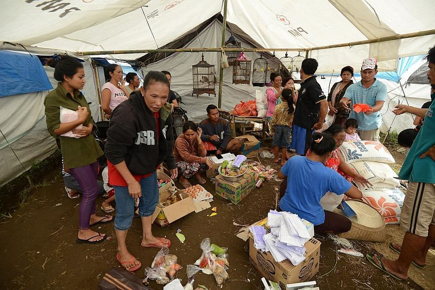 Right: A banner map put up to show the danger zone around Mount Agung, warning people not to enter it. Far right: Evacuees getting their food rations at a temporary shelter in Karangasem district.