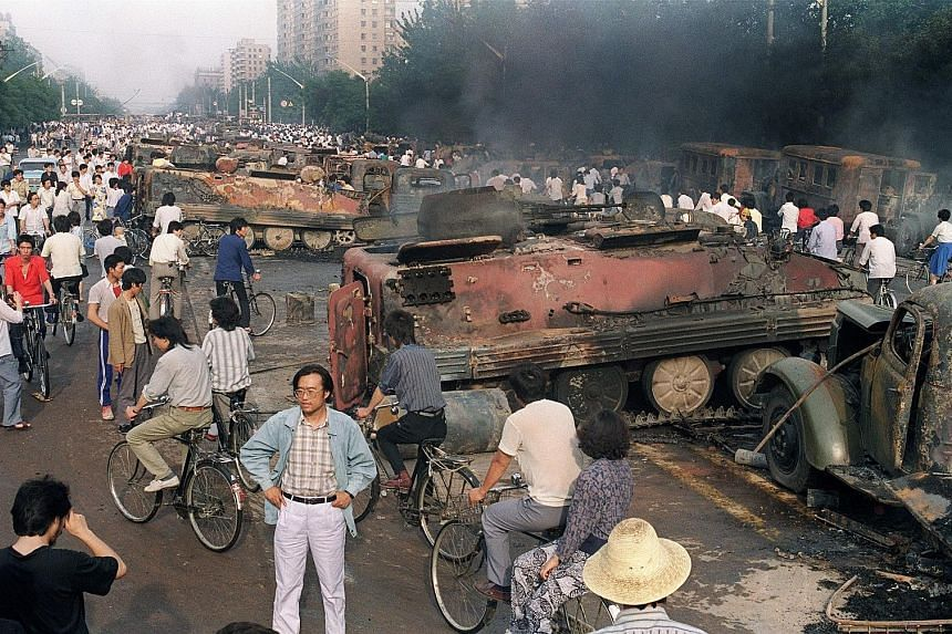 Beijing residents gathering around the smoking remains of over 20 armoured personnel carriers burned by demonstrators during clashes with soldiers near Tiananmen Square on June 4, 1989.