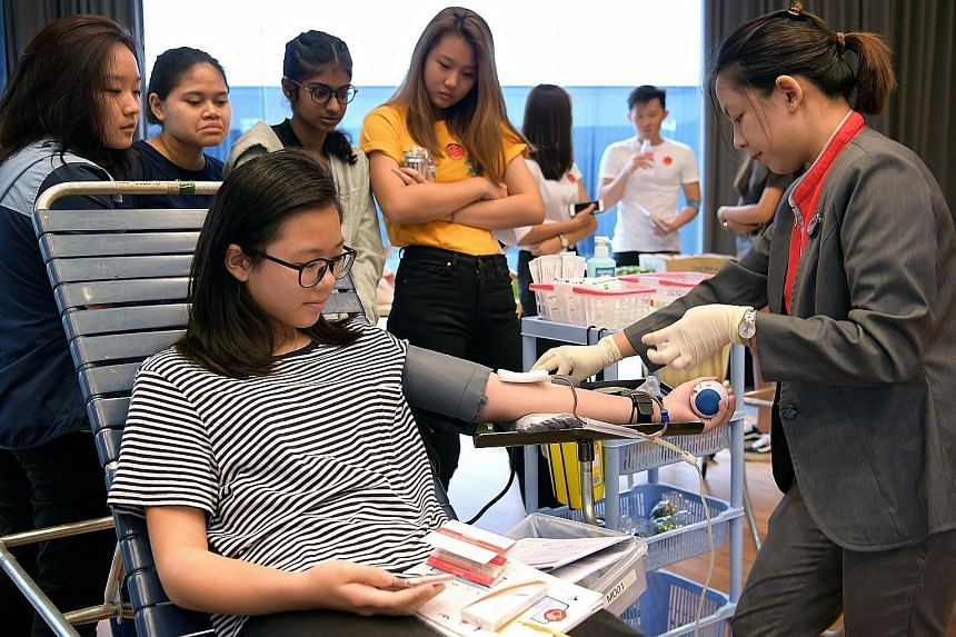 Student Hilda Lam, 16, donating blood at *Scape in Orchard Road yesterday as part of a drive to encourage more young Singaporeans to give blood. Standing behind her are her schoolmates (from left) Leia Sim, Farjana Begum, Nadra Kamal and Lim Si Yun,