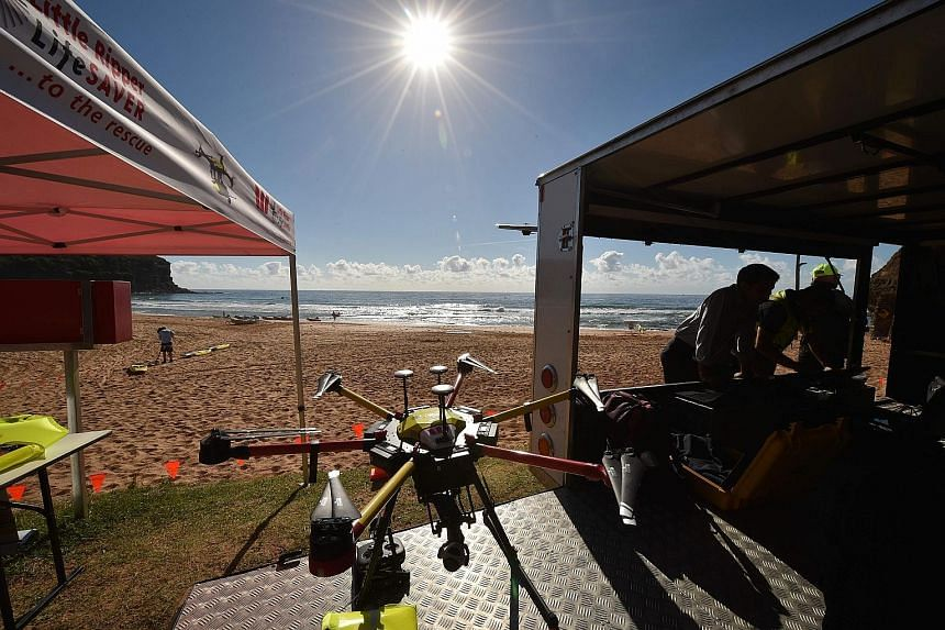 A shark-spotting drone (above), at Bigola beach north of Sydney, which is able to obtain aerial images of sharks in the water (below) and alert beachgoers to danger.