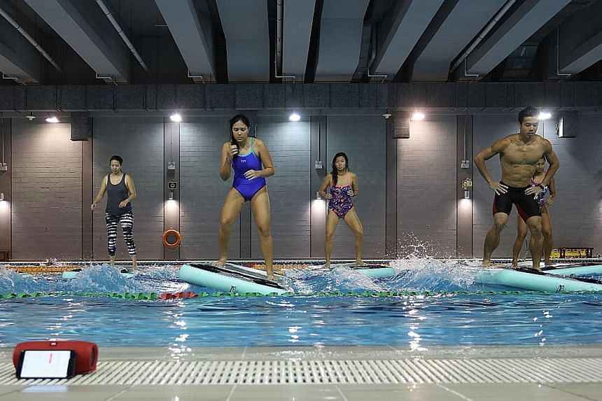 Participants exercising on a floating Boga FitMat during a HydroFit class in a training pool at the OCBC Aquatic Centre.