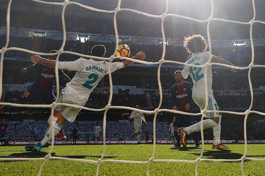 Left: Barcelona forward Luis Suarez celebrating after opening the scoring in the 54th minute in the Clasico against Real Madrid at the Santiago Bernabeu yesterday. Below: Real Madrid right-back Dani Carvajal handling the ball in the box in the 63rd m