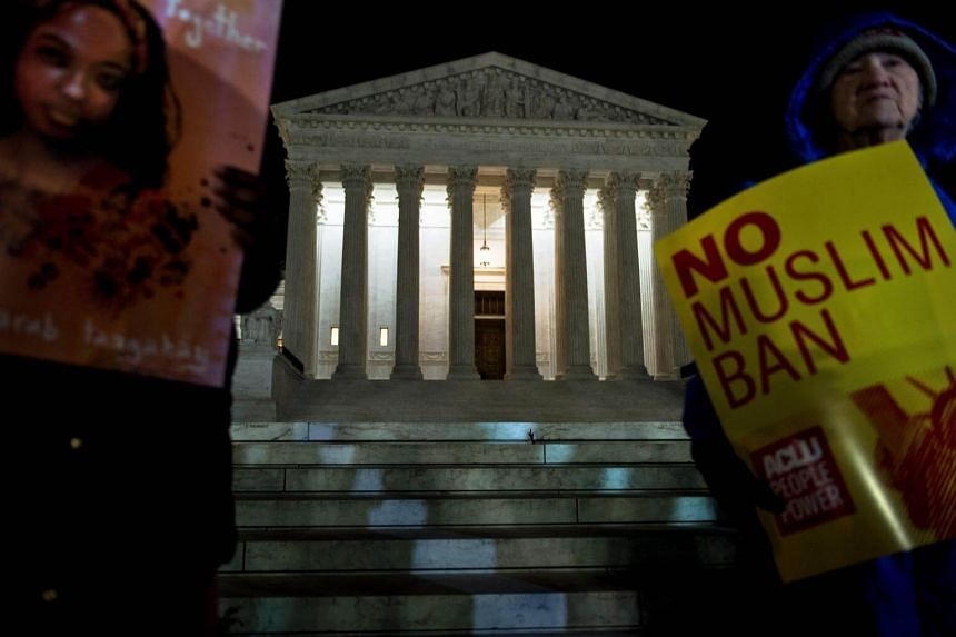Activists protest the travel ban outside the US Supreme Court in Washington, DC, on Dec 7, 2017.