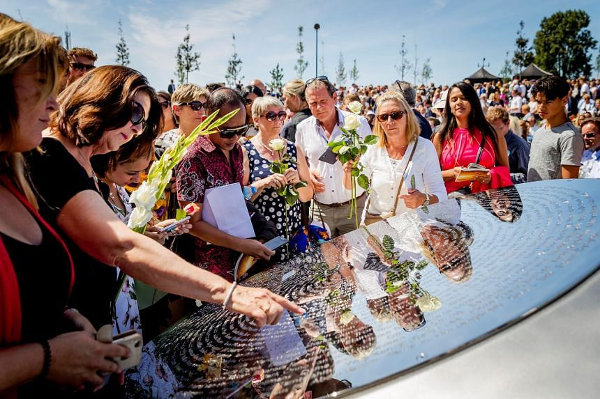 Relatives of those on board Malaysia Airlines flight MH17 looking at the victims' names on a memorial in Vijfhuizen, Netherlands, on July 17, 2017.