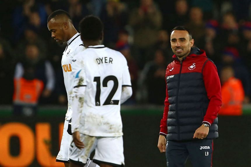 Swansea City's Interim manager Leon Britton congratulates his players on the pitch.