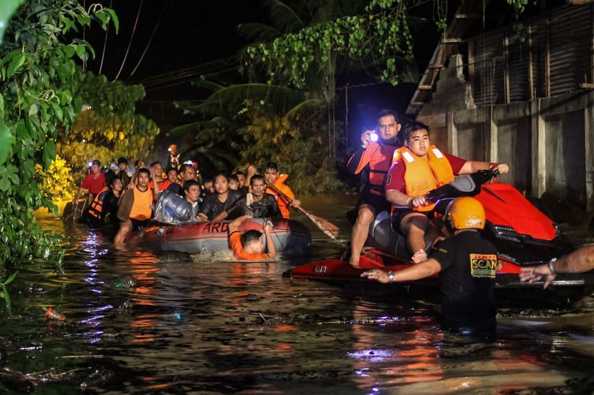 Rescue workers evacuating affected residents early yesterday. The people had received ample warnings, but as they were rarely hit by typhoons, those living near the rivers did not take them seriously, said Salvador police chief Wilson Mislores.