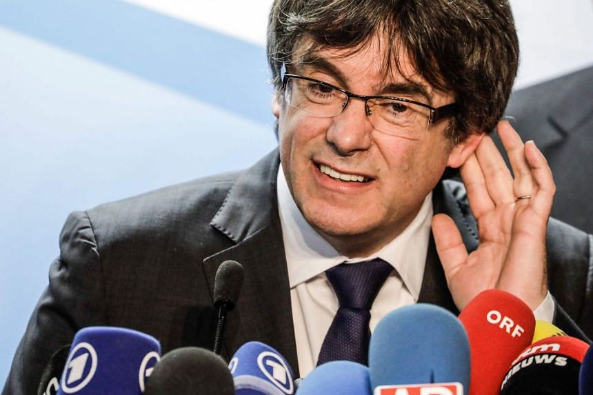 Carles Puigdemont gestures during a press conference in Brussels, a day after Catalonia's regional election.