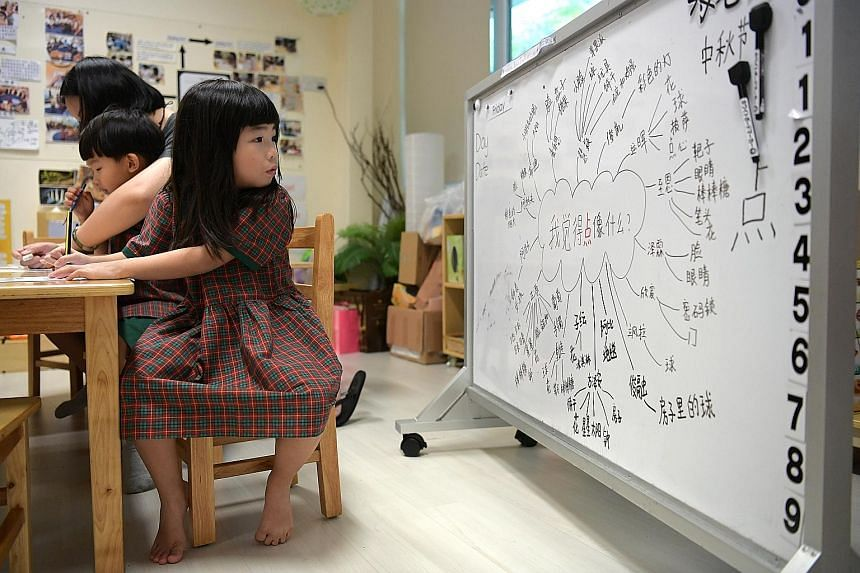 """Children at EtonHouse pre-school in Upper Bukit Timah Road producing """"provocation pages"""" in Chinese with the help of a mind map. They are thinking about the Chinese character """"dian"""" and what it reminds them of."""