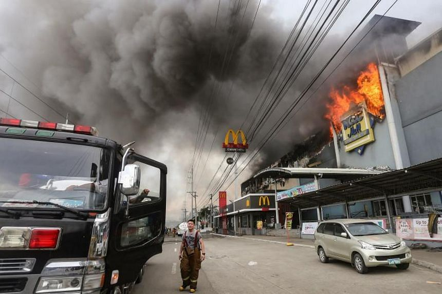 Smoke billows out from the NCCC Mall in Davao city after a fire broke out, on Dec 23, 2017.