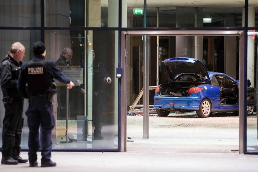 Police officers inspecting the damage in the lobby of the German Social Democratic Party (SPD) headquarters after a man drove his car into the building, on Dec 25, 2017.