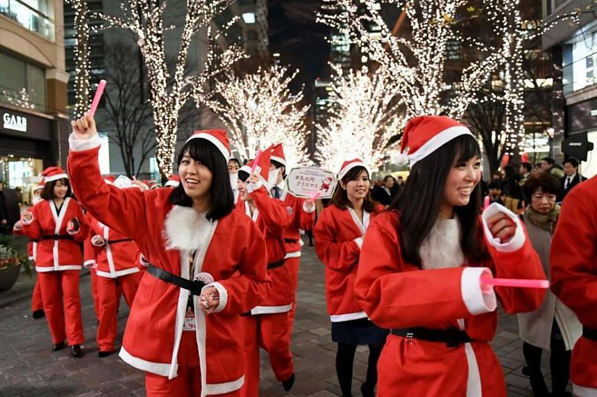 Shop clerks and workers taking part in a Christmas parade at the Marunouchi shopping district in Tokyo on Dec 22, 2017.