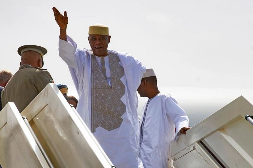 Malian former president Amadou Toumani Toure waves while disembarking from a plane in Bamako on Dec 24, 2017, as he returns for the first time to Mali from living in exile in Senegal since a coup deposed him in 2012.