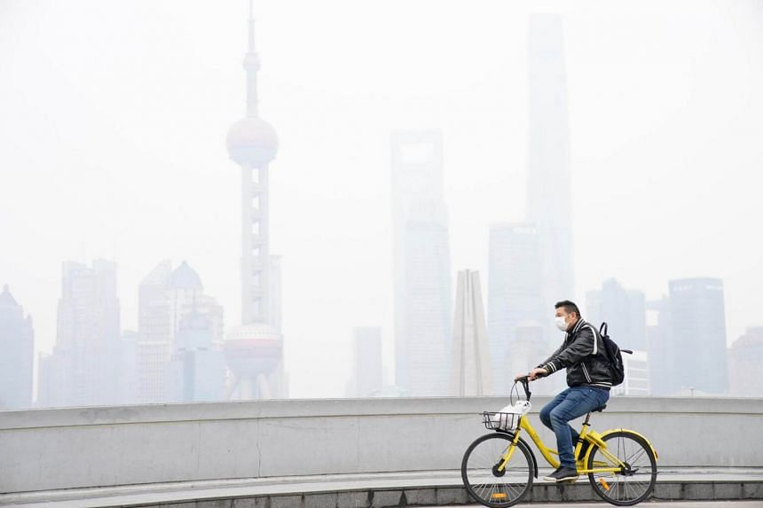 A man wears a face mask while riding a bicycle on a polluted day in Shanghai, China, on Nov 22.