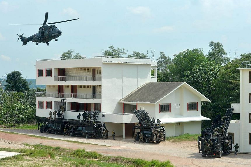 Special forces teams storming a simulated terrorist hideout in buildings during a land operation drill at a training area in Lim Chu Kang on May 9, 2016.