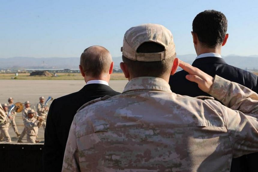 Russian President Vladimir Putin and Syrian President Bashar al-Assad inspecting a military parade at the Russian air base in Hmeimim, Syria, on Dec 11, 2017.
