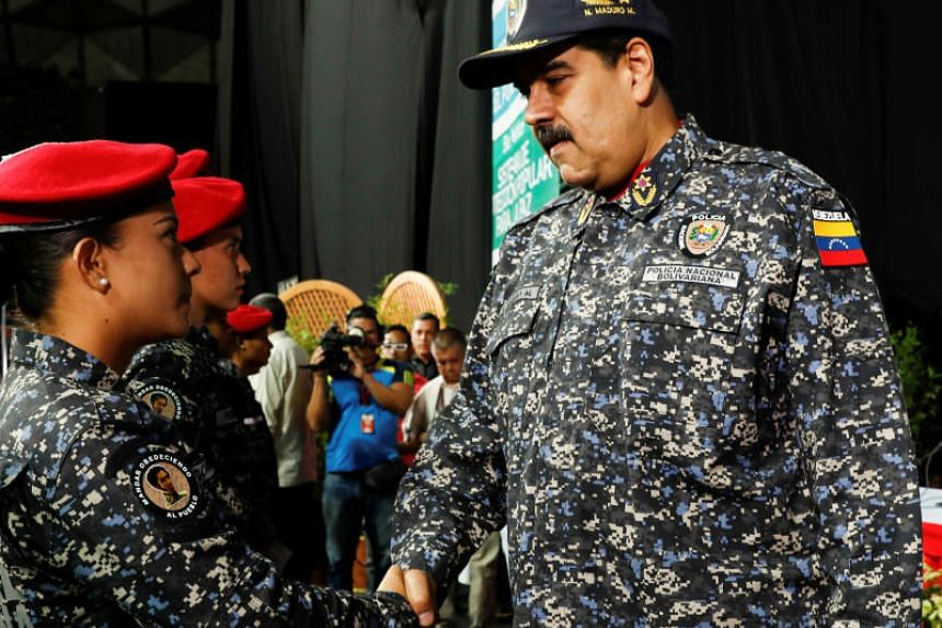 Venezuela's President Nicolas Maduro (right) shakes hands with a newly graduated policewoman during a Bolivarian National Police officers' graduation ceremony in Caracas, Venezuela on Dec 20, 2017.