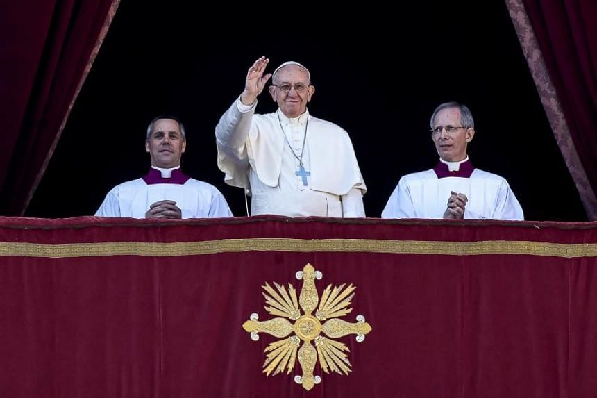 Pope Francis waves to the faithful as he delivers the traditional Urbi et Orbi (to the city and to the world) Christmas Day message from the central balcony of St. Peter's Basilica at the Vatican on Dec 25, 2017.