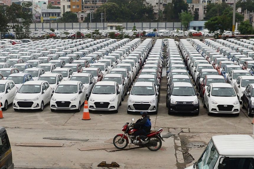 An Indian motorist rides past parked Hyundai vehicles ready for shipment at a port in Chennai on Dec 1.