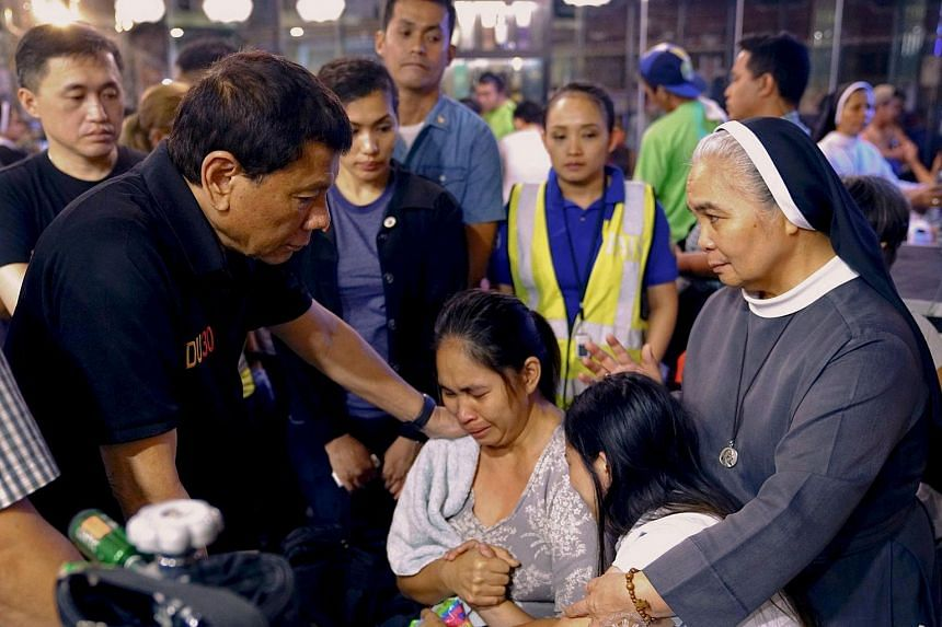 Philippines' President Rodrigo Duterte (left) comforting a relative of one of the victims after a fire engulfed a shopping mall in Davao City on the southern Philippine island of Mindanao