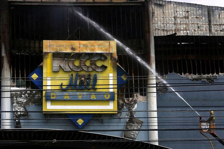 A fireman uses a water hose at the shopping mall hit by fire in Davao city in Philippines.