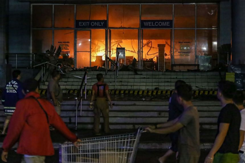 People looking at the fire at a shopping mall in Davao City on the southern Philippine island of Mindanao.