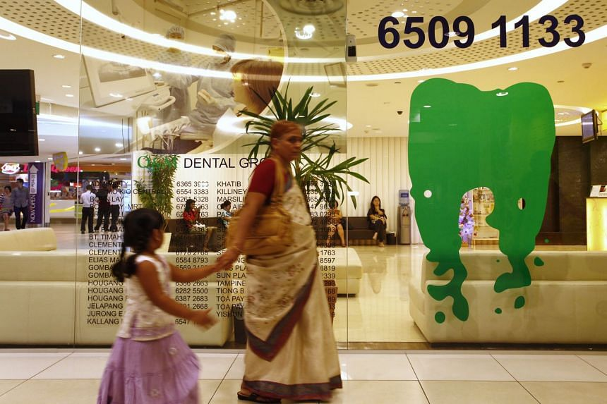 Shoppers walk past a Q&M dental clinic located in City Square Mall.