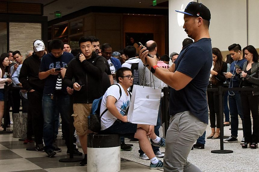 A man leaving an Apple Store in Los Angeles with his new iPhone X as others wait to buy theirs on Nov 3, when it was released. Analysts have cut iPhone X shipment projections for the first quarter of next year.