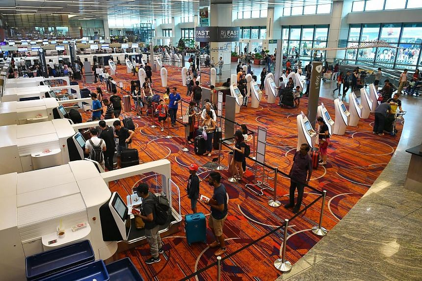 Above and left: A group of 30 check-in kiosks and 20 baggage drop-off machines in the centre of the departure hall at Changi Airport's Terminal 1. More self-service counters have been unveiled at the terminal in an effort to boost efficiency and redu