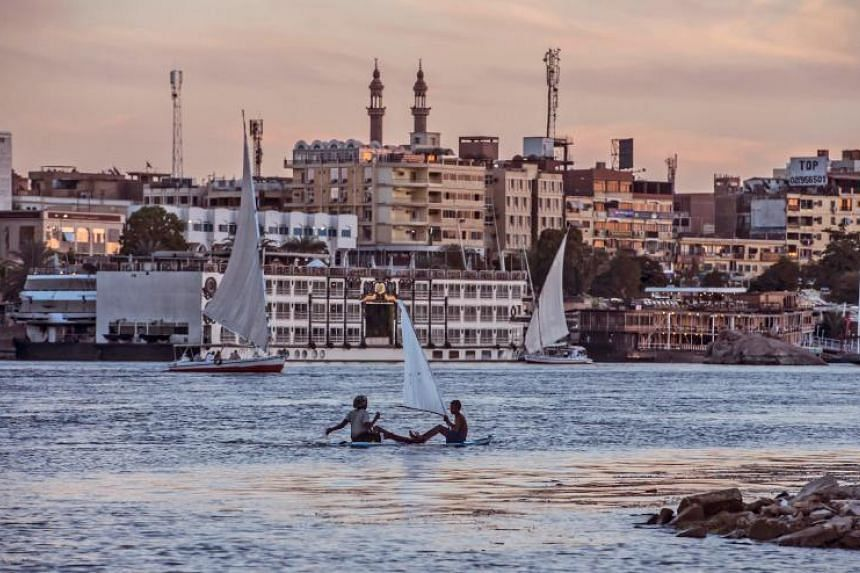 Egyptian children sit on a surfboard with an improvised sail in the Nile river in the southern city of Aswan, some 920 kilometres away from the capital Cairo on Nov 24, 2017.