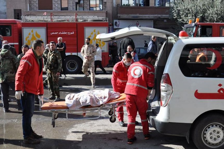 Members of the Syrian Arab Red Crescent loading a body into an ambulance following a car bomb explosion in a predominantly pro-government neighbourhood of the central Syrian city of Homs on Dec 5, 2107.
