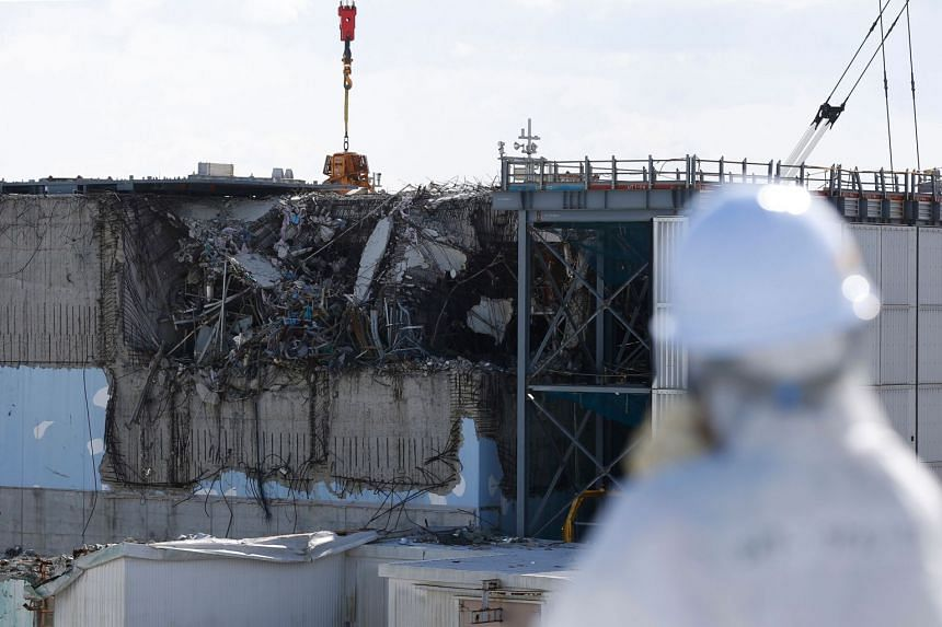 A member of the media, wearing a protective suit and a mask, looking at the No. 3 reactor building during a press tour at Tokyo Electric Power Co's nuclear power plant in Fukushima.