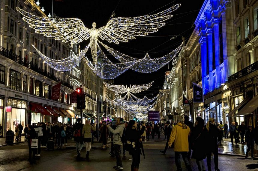 Holidaymakers enjoying the Christmas lights of Regent Street, one of London's most famous shopping streets.