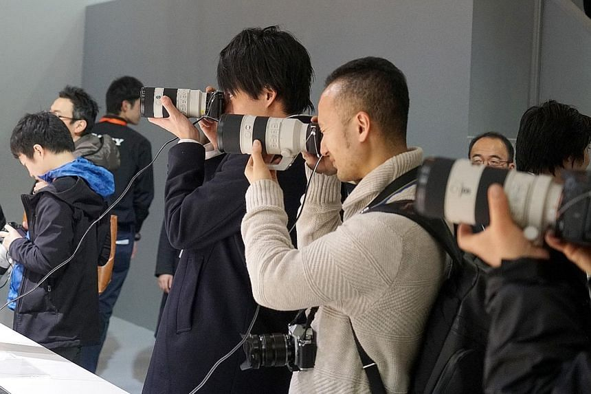 Visitors trying products at the CP+ Camera and Imaging Show in Yokohama in February.