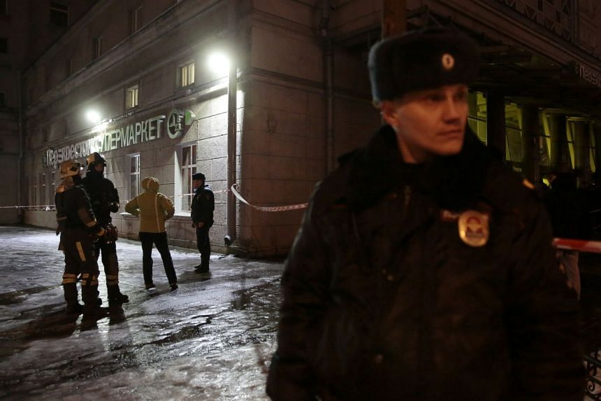 Officials and police officers outside the St Petersburg supermarket.