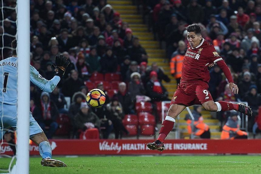 Liverpool's Brazilian midfielder Roberto Firmino volleying the ball from a Philippe Coutinho cross to score their second goal against Swansea at Anfield on Tuesday. They ran out 5-0 winners against the bottom side.