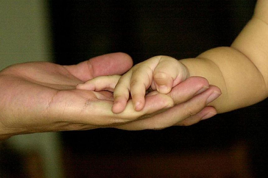 "File photo of an adult holding a child's hand. The Ministry of Social and Family Development said its position is ""informed by Singapore's public policy, which encourages parenthood within marriage""."