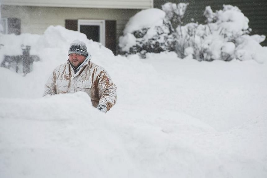 Erie resident Thomas Berry removes snow from the sidewalk in front of his home after two days of record-breaking snowfall.