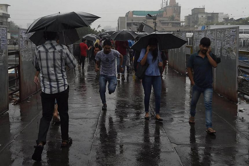 Indian commuters protect themselves during rain from the cyclone Ochki in Mumbai, on Dec 5, 2017.