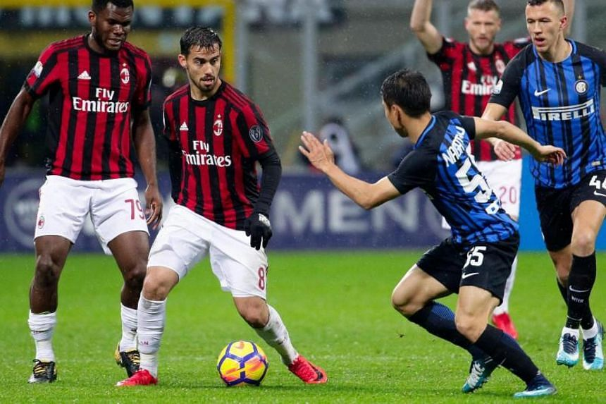 Milan's Suso (center) and Inter's Yuto Nagatomo (right) in action during the Italy Cup quarter-final soccer match AC Milan vs Inter FC at Giuseppe Meazza stadium in Milan, Italy, Dec 27, 2017.