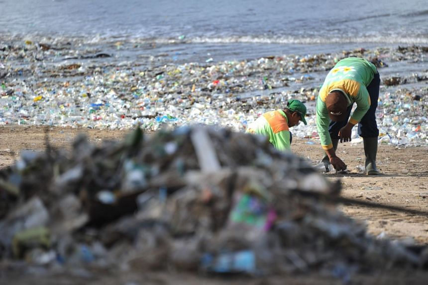 Rubbish collectors clearing trash on Kuta beach near Denpasar, on Indonesia's tourist island of Bali.